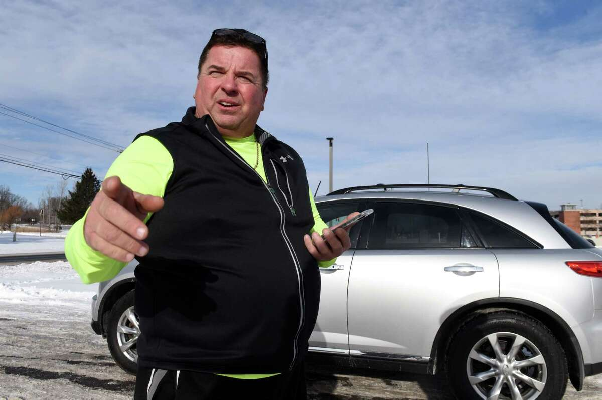Lyft driver Christopher Sokol of Clifton Park describes his driver experiences while waiting for fares at the ride-hailing parking lot near Albany International Airport on Friday, Dec. 29, 2017, in Colonie, N.Y. Uber and Lyft will be available on New Year's for the first time in the Capital Region. (Will Waldron/Times Union)