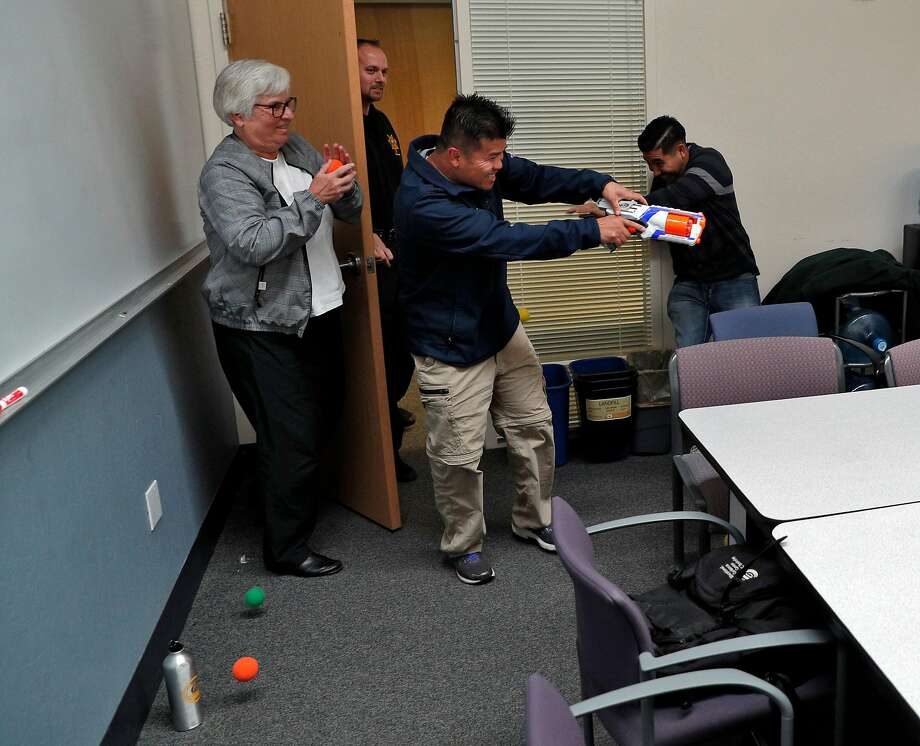 UC Berkeley assistant vice chancellor Marsha Jaeger (left) and Juan Manriquez (right) defend themselves against the shooter, played by partnerships educator Boun Khamnouane. Photo: Carlos Avila Gonzalez, The Chronicle