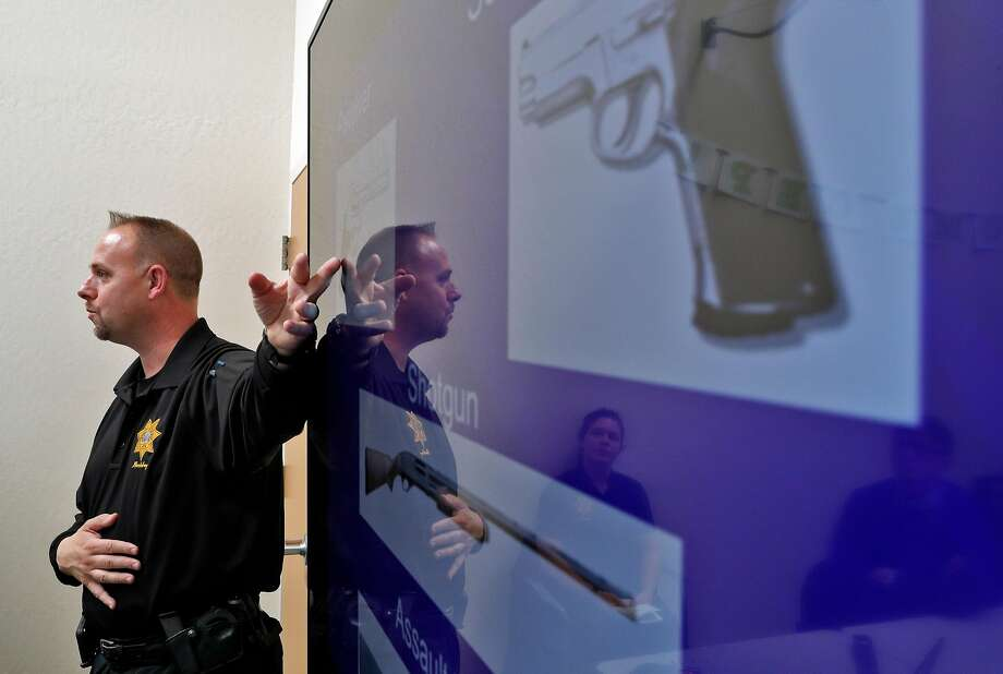 Cpl. Wade MacAdam shows students slides of weapons for identification during an active shooter training session at UC Berkeley. Photo: Carlos Avila Gonzalez, The Chronicle