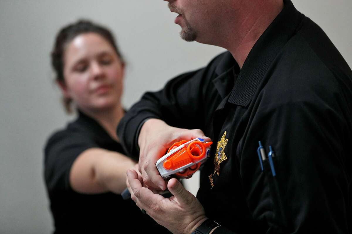 Cpl. Wade McAdam, right, demonstrates the best way to immobilize a weapon held by Sgt. Sabrina Reich, left, as they role play with a toy gun during an active shooter training session presented by the UC Police on the UC Berkeley campus in Berkeley, Calif., on Tuesday, December 12, 2017.