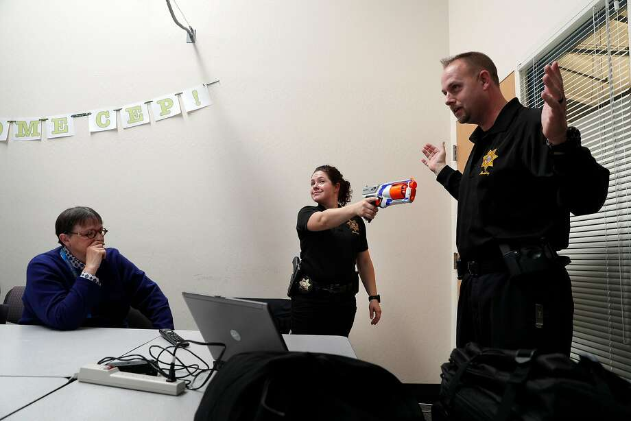 UC Berkeley police Sgt. Sabrina Reich holds a toy gun while playing the role of the shooter as Cpl. Wade MacAdam reacts during a training session. Photo: Carlos Avila Gonzalez, The Chronicle
