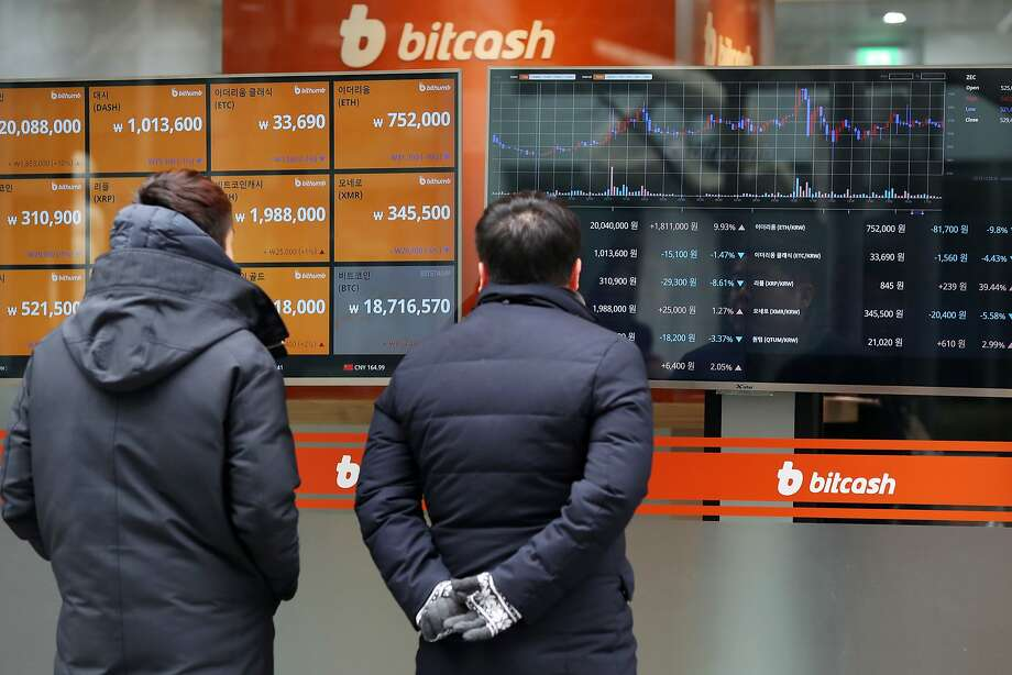 People check on the monitors showing the prices of digital currencies at the Bithumb exchange in Seoul. Photo: SeongJoon Cho, Bloomberg