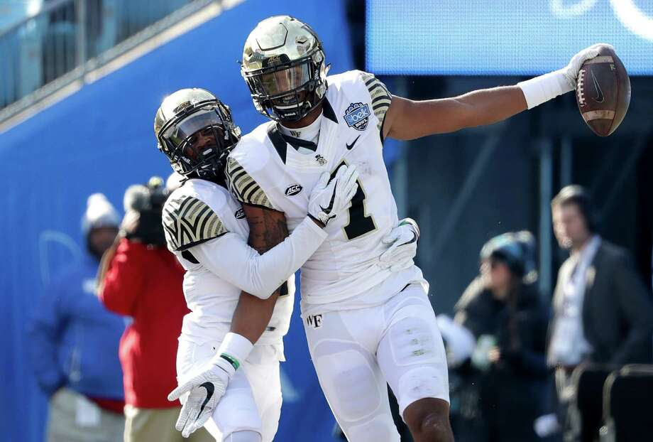 CHARLOTTE, NC - DECEMBER 29:  Scotty Washington #7 of the Wake Forest Demon Deacons celebrates catching a touchdown with teammate Tabari Hines #1 against the Texas A&M Aggies during the Belk Bowl at Bank of America Stadium on December 29, 2017 in Charlotte, North Carolina. Photo: Streeter Lecka, Getty Images / 2017 Getty Images