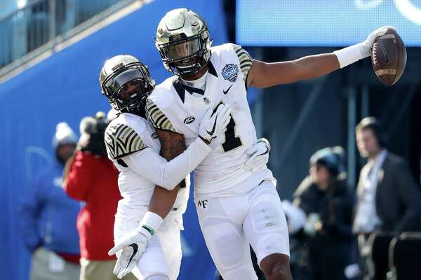 CHARLOTTE, NC - DECEMBER 29:  Scotty Washington #7 of the Wake Forest Demon Deacons celebrates catching a touchdown with teammate Tabari Hines #1 against the Texas A&M Aggies during the Belk Bowl at Bank of America Stadium on December 29, 2017 in Charlotte, North Carolina.