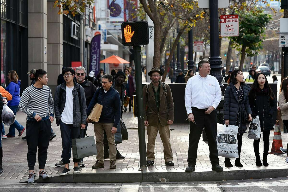 Pedestrians wait for the signal to change before crossing 5th Street in San Francisco, Calif., on Thursday December 28, 2017.