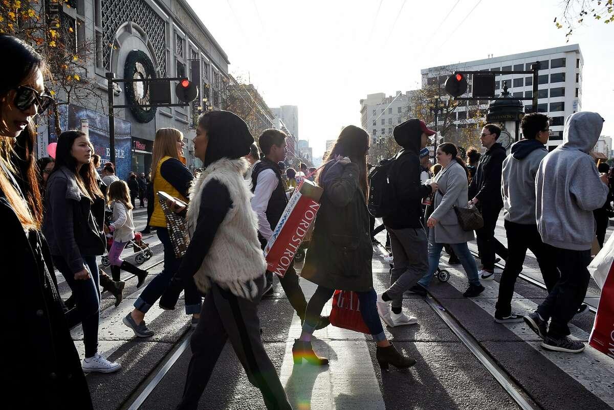 Pedestrians use a crosswalk to cross Market Street in San Francisco, Calif., on Thursday December 28, 2017.