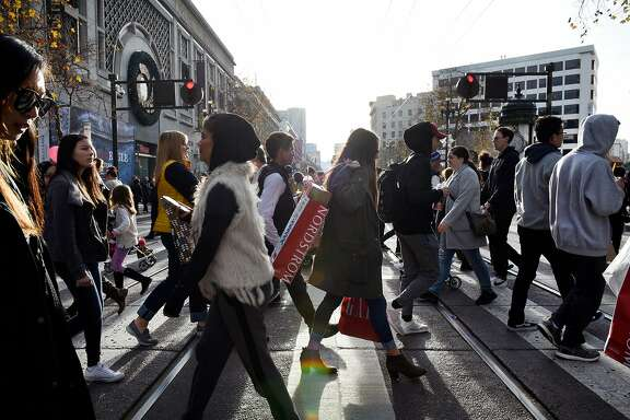 Pedestrians use a crosswalk to cross Market Street in San Francisco, Calif., on Thursday December 28, 2017.