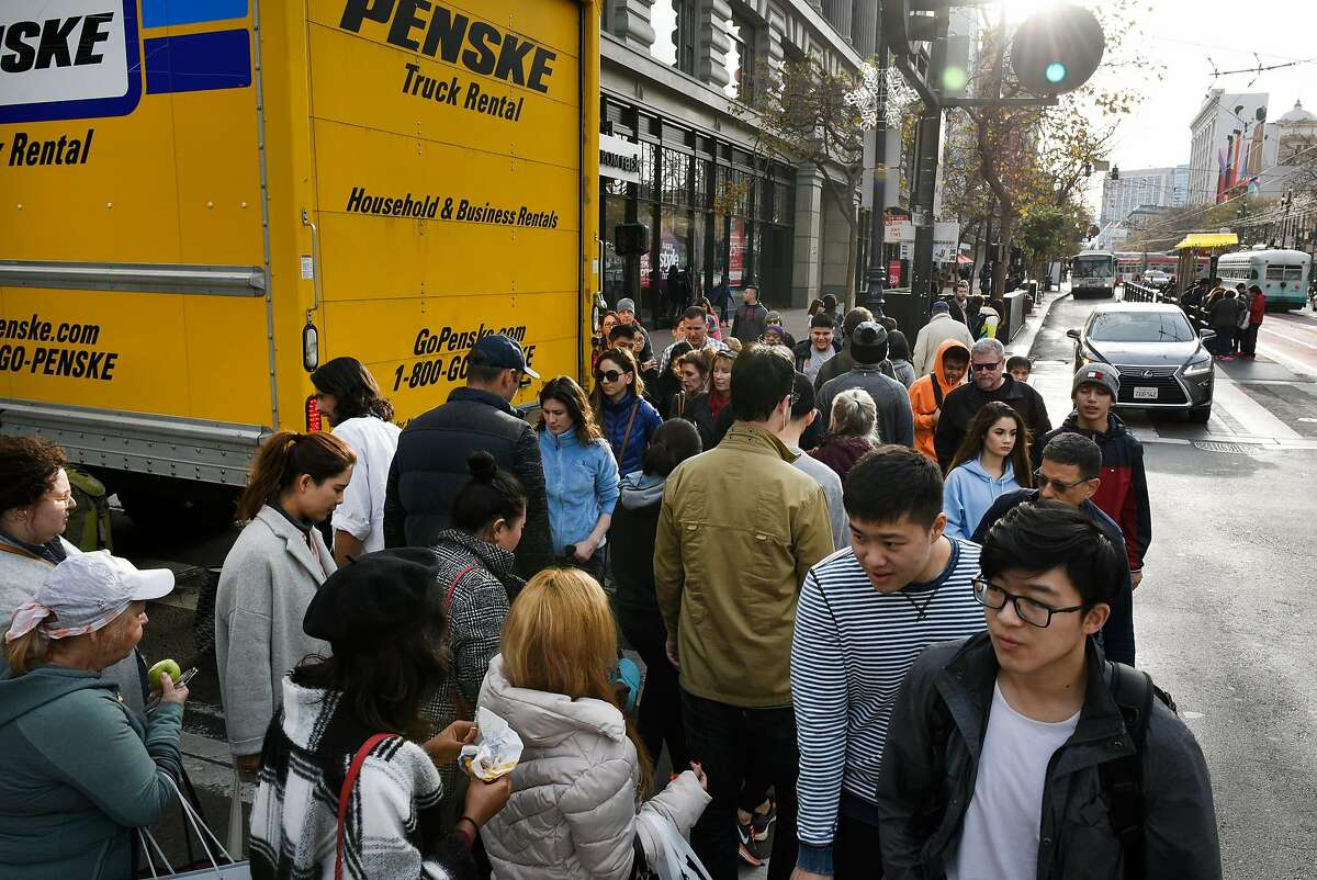 Pedestrians squeeze past a truck stopped in the crosswalk as they try to cross 5th Street in San Francisco, Calif., on Thursday December 28, 2017.