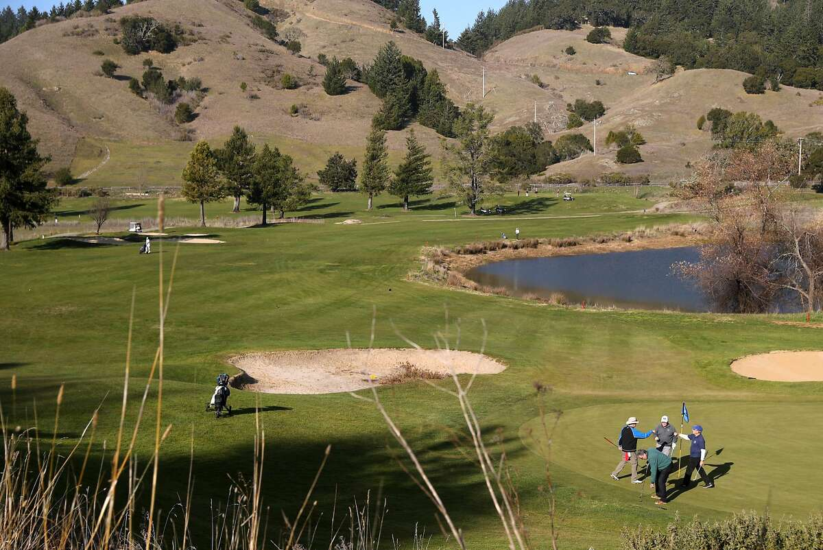 Tom Faimali of San Rafael (right) fist bumps with his playing partners on the 18th green after finishing their round at San Geronimo Golf Course in San Geronimo, Calif., on Monday, December 18, 2017.