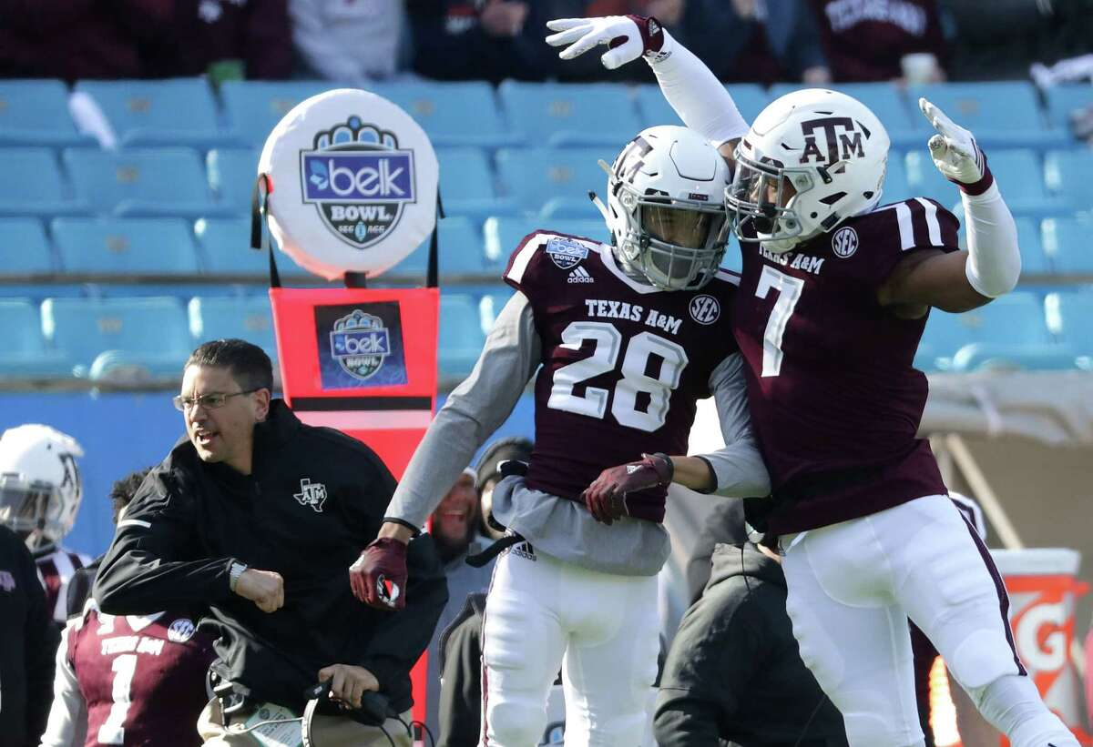 CHARLOTTE, NC - DECEMBER 29: Interim head coach Jeff Banks reacts with players Travon Fuller #28 and Buddy Johnson #7 of the Texas A&M Aggies after a play against the Wake Forest Demon Deacons during the Belk Bowl at Bank of America Stadium on December 29, 2017 in Charlotte, North Carolina.