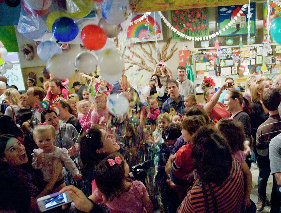 Children and parents celebrate as balloons and confetti drop from the ceiling during The Woodlands Childrens Museum's High Noon Countdown. / Staff photo by Eric S. Swist