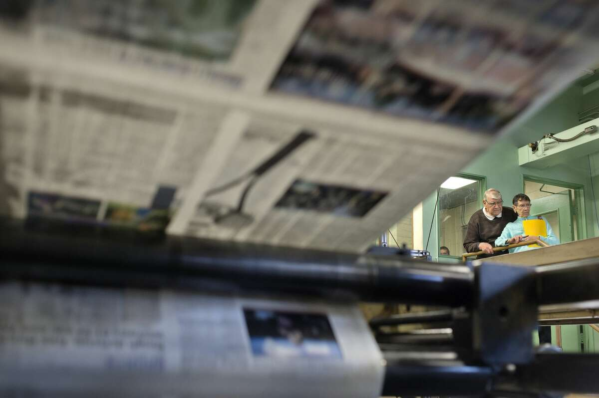 Retired Midland Daily News press foreman Larry Sabourin and his wife Carol watch as the last Friday paper is printed on the Goss Urbanite offset press Friday morning, Feb. 3. Sabourn started working at the Daily News in 1951 after he graduated from high school and retired in 1995. Starting Feb. 6, the printing operations moved to Big Rapids. (Brittney Lohmiller/Midland Daily News)
