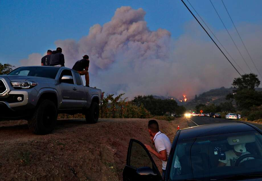 Members of the community watch as a fire grows along the ridge neaer Highway 12 outside Eldridge, Calif., on Tuesday, October 10, 2017. The Napa and Sonoma valleys continue to be under threat from several fires as some communities begin  to assess the impact of the fires. Photo: Carlos Avila Gonzalez, The Chronicle