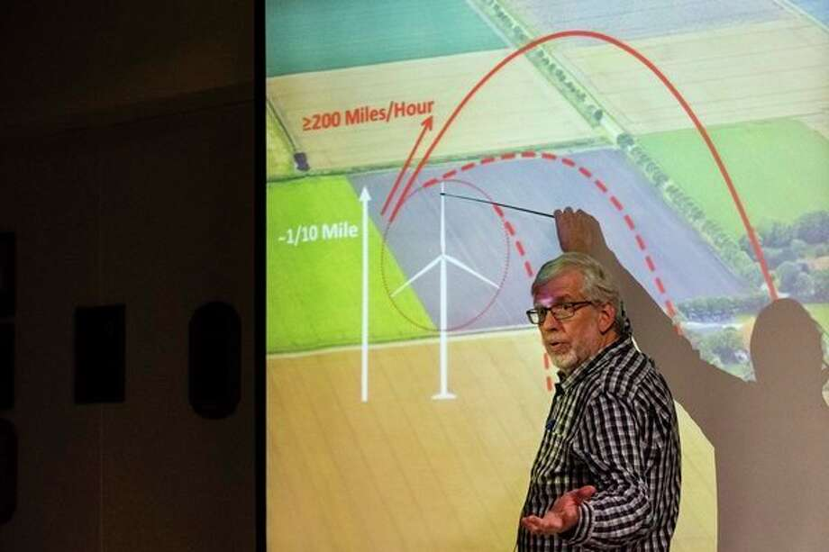 David Moll shows a graphic estimating the distance ice or debris could be thrown from turbine blades during a wind energy informational meeting sponsored by Ingersoll Township Concerned Citizen, on Nov. 16 at Bullock Creek High School. (Danielle McGrew Tenbusch/for the Daily News) / ©2017