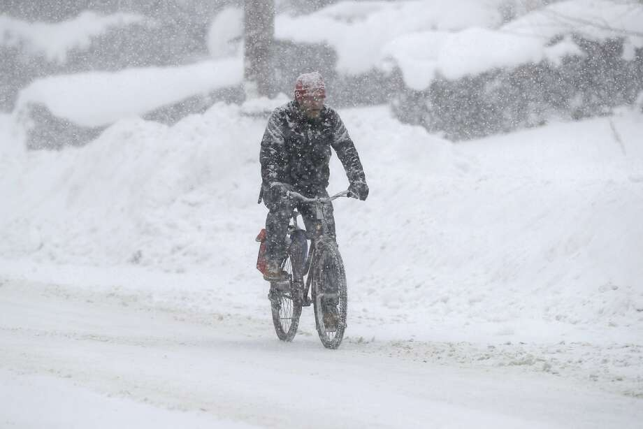 A cyclist tries to navigate the hazards in Erie, Pa. The brutal weather is blamed for several deaths and numerous crashes. Photo: Tony Dejak, Associated Press