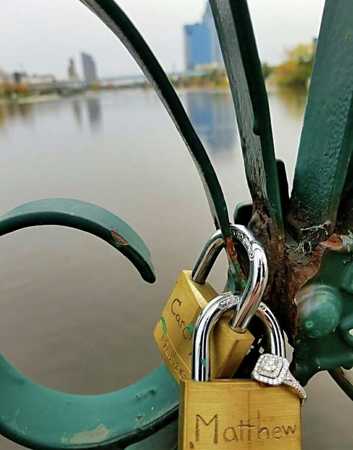 Carolyn Milco's engagement ring is attached to the locks that the couple had secured to a bridge in Grand Rapids months before. When they returned to the bridge five months later, Carolyn had no idea her boyfriend Matthew Love was about to propose. (photo provided)