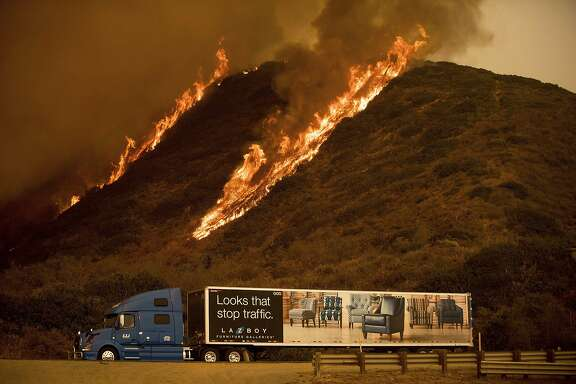 Flames from the Thomas fire burn on a hillside behind a truck on Highway 101 north of Ventura, Calif., on Wednesday, Dec. 6, 2017. Ferocious winds whipped sparks into massive infernos that have destroyed hundreds of buildings and forced hundreds of thousands of people to flee since Monday. (AP Photo/Noah Berger)