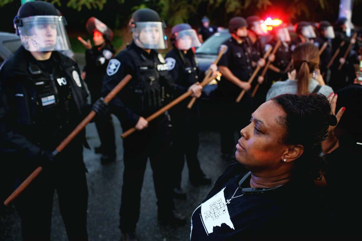 Cousin of Charleena Lyles, Robin Cockerherm, right, eyes a police barricade as hundreds marched from Magnuson Park to the Montlake Bridge after a vigil, Tuesday, in honor of Lyles, who was fatally shot by police Sunday morning, June 20, 2017. (Genna Martin, seattlepi.com)