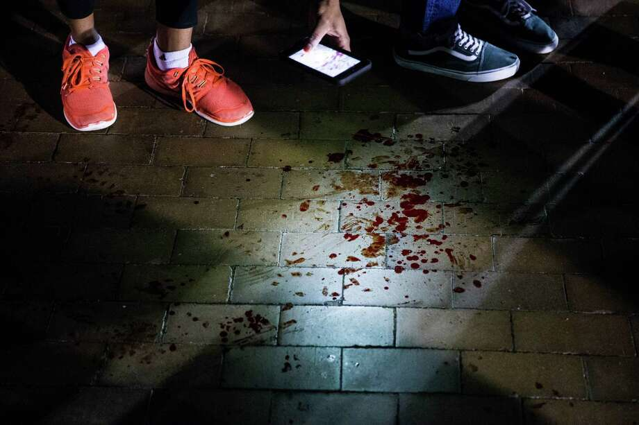 People photograph blood on University of Washington's Red Square after a protester was shot during demonstrations against controversial Breitbart.com editor Milo Yiannopoulos' speech that evening on campus, on Jan. 20. Photo: GRANT HINDSLEY/SEATTLEPI.COM