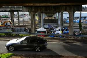 A Tesla drives past a homeless encampment under the south end of the Ballard Bridge, March 1, 2017. The city announced plans this week to clear the camp away. About six people are still living at the camp. (Genna Martin, seattlepi.com)