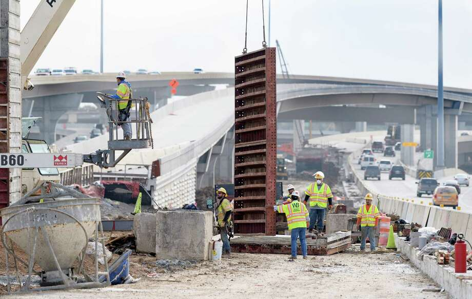 Workers remove a form from a new sign post during construction on U.S. 290 on Dec. 21 near Loop 610. Photo: Wilf Thorne / © 2017 Houston Chronicle