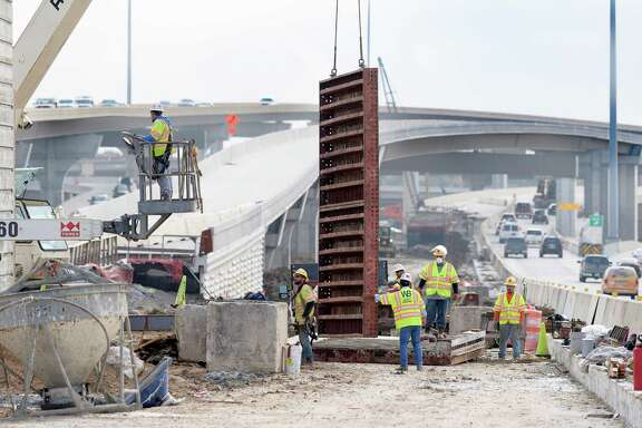 Workers remove a form from a new sign post during construction on U.S. 290 on Dec. 21 near Loop 610.