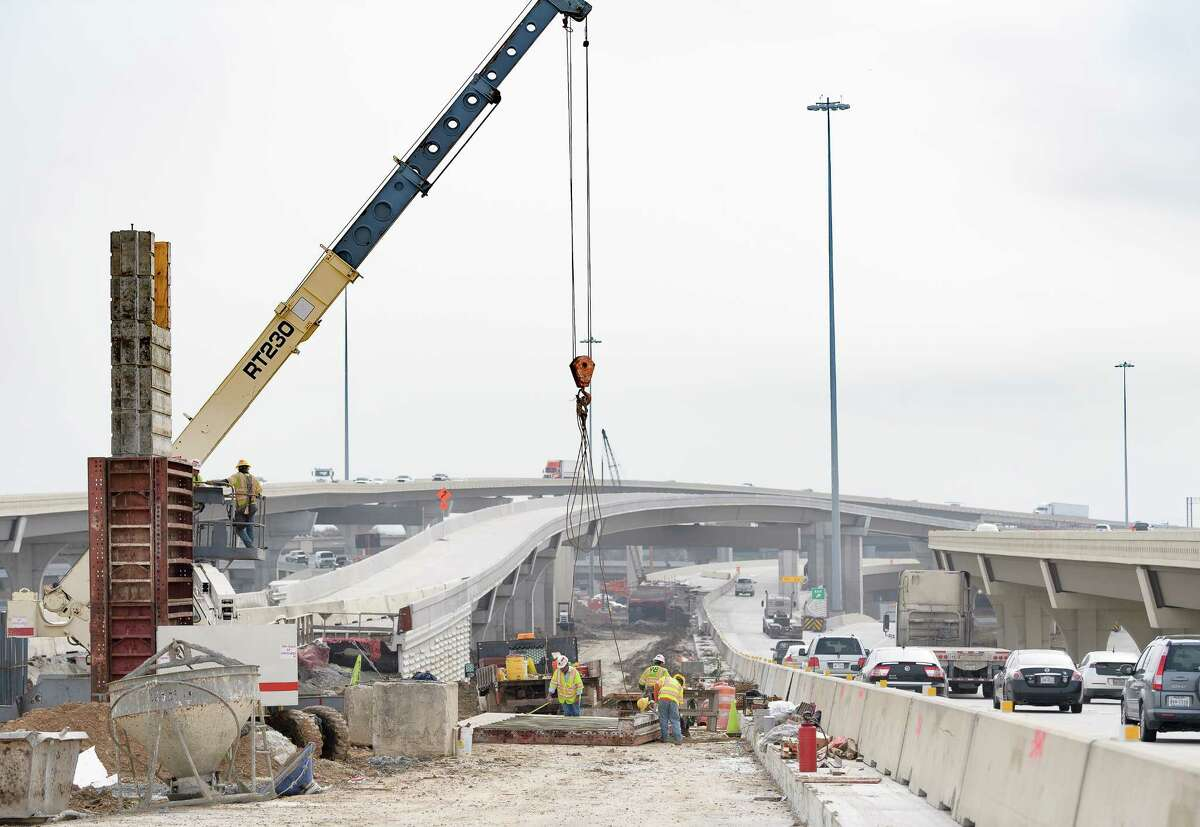 Workers remove a form from a new sign post during constructionon U.S. 290 on Dec. 21 near Loop 610.