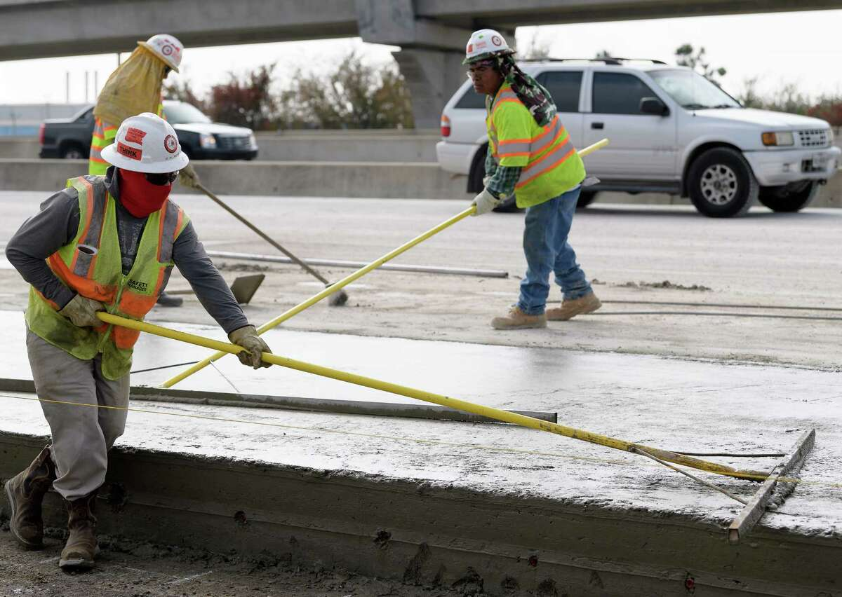 Workers smooth out freshly poured concrete on the westbound lane of U.S. 290 on Dec. 21 near Elderidge.