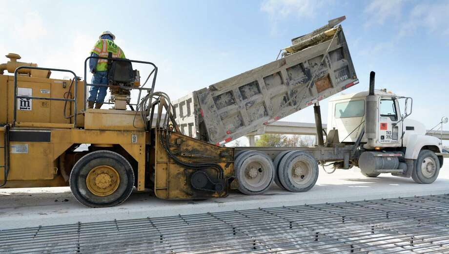 Workers use poured concrete and a slip form paving machine to build new lanes along westbound U.S. 290 on Dec. 21 near Eldridge. Photo: Wilf Thorne / © 2017 Houston Chronicle