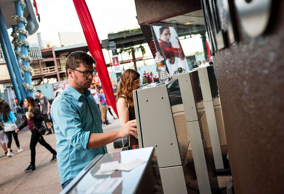Dan Lanini, who buys tickets with MoviePass, uses a ticket kiosk at the AMC Disney Springs 24 in Florida. MoviePass offers subscribers the chance to go to the movies 365 times a year for $9.95 a month. Photo: JACOB LANGSTON, NYT