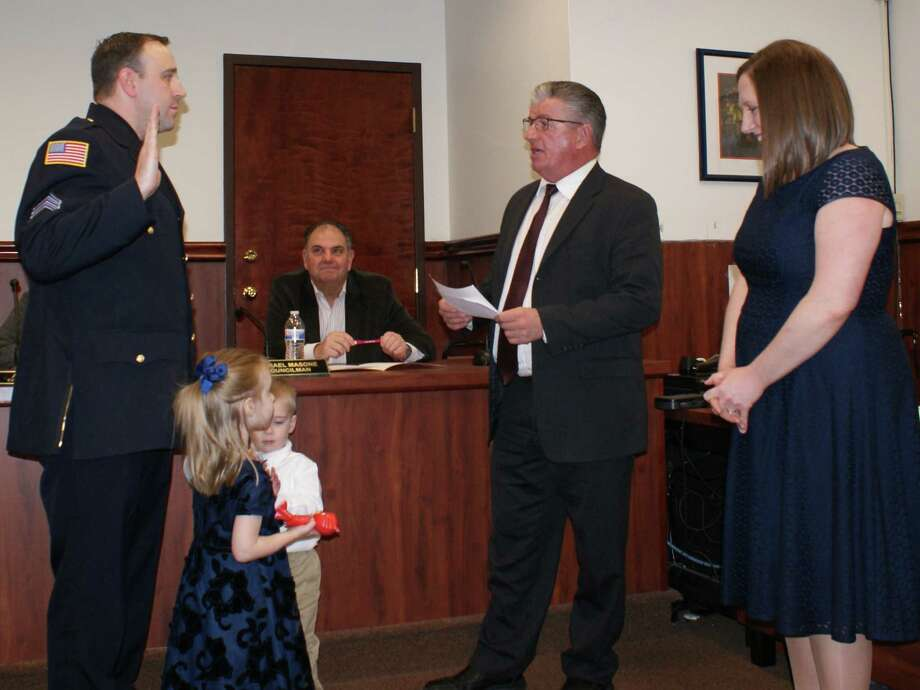 North Greenbush Supervisor Lou Desso administers the oath to Sgt. Dave Keevern to become the town's next chief of police. Holding the bible are his children Emily and David Jr. while his wife Jen looks in. In the background is Councilman Mike Masone. (Photo provided)