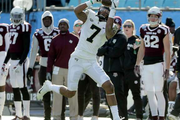 Wake Forest's Scotty Washington (7) catches a touchdown pass against Texas A&M during the first half of the Belk Bowl NCAA college football game in Charlotte, N.C., Friday, Dec. 29, 2017. (AP Photo/Chuck Burton)