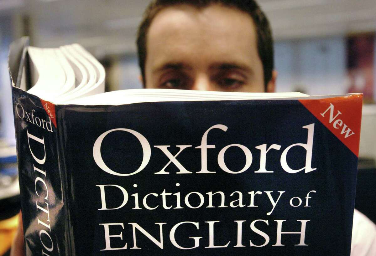 A man reads a copy of the Oxford Dictionary of English, which recognized the power of the millennial generation with its 2017 word of the year: youthquake, the worst choice in quite a while.