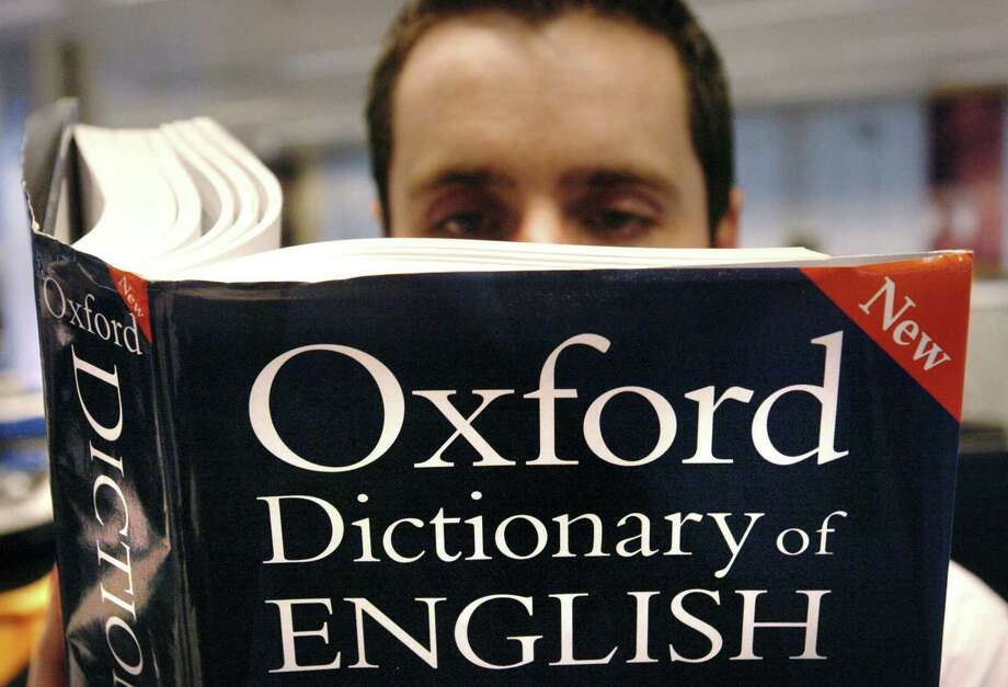 A man reads a copy of the Oxford Dictionary of English, which recognized the power of the millennial generation with its 2017 word of the year: youthquake, the worst choice in quite a while. Photo: Ian Nicholson /Associated Press / PA
