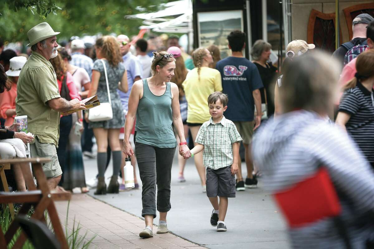 The Woodlands resident Faye Geiger, left, and her 7-year-old son Ethan stroll through the Woodlands Waterway Arts Festival on Sunday, April 10, 2016. This year's festival is scheduled for April 7-8.
