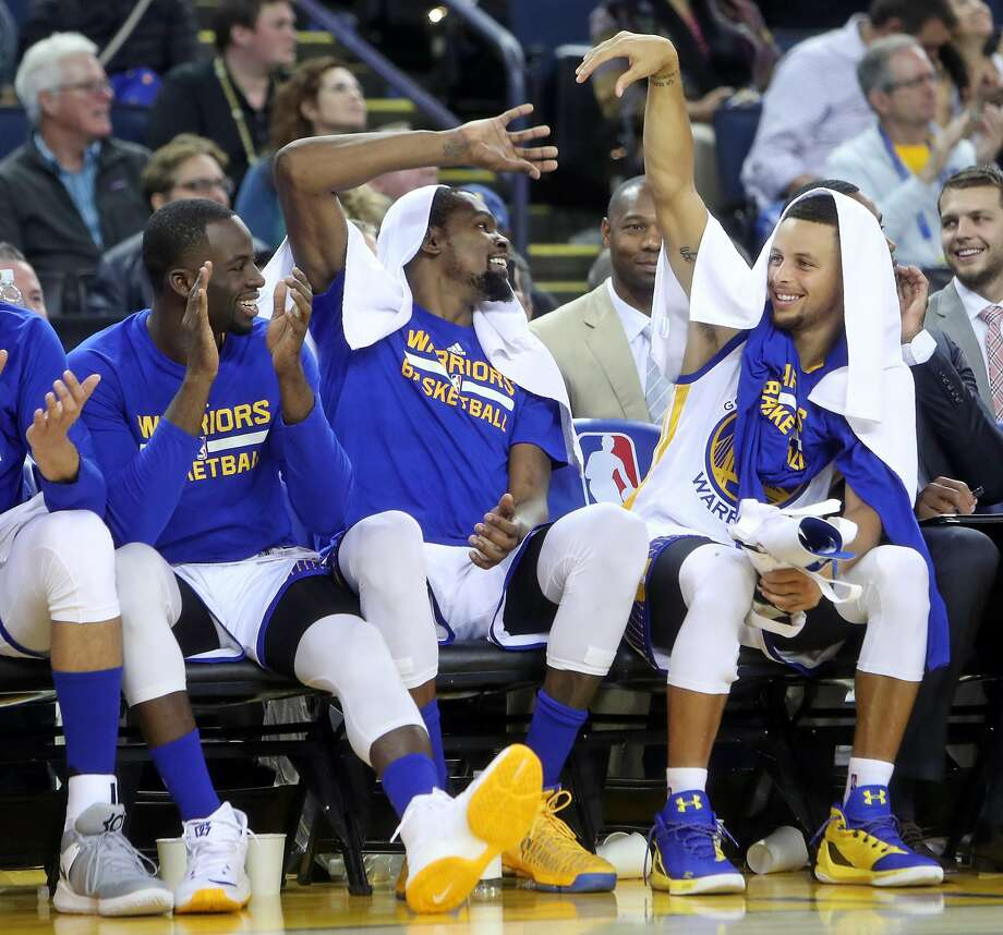 Golden State Warriors' Draymond Green, Kevin Durant and Stephen Curry enjoy final minutes of 122-96 win over Oklahoma City Thunder in NBA game at Oracle Arena in Oakland, Calif., on Thursday, November 3, 2016. Photo: Scott Strazzante, The Chronicle