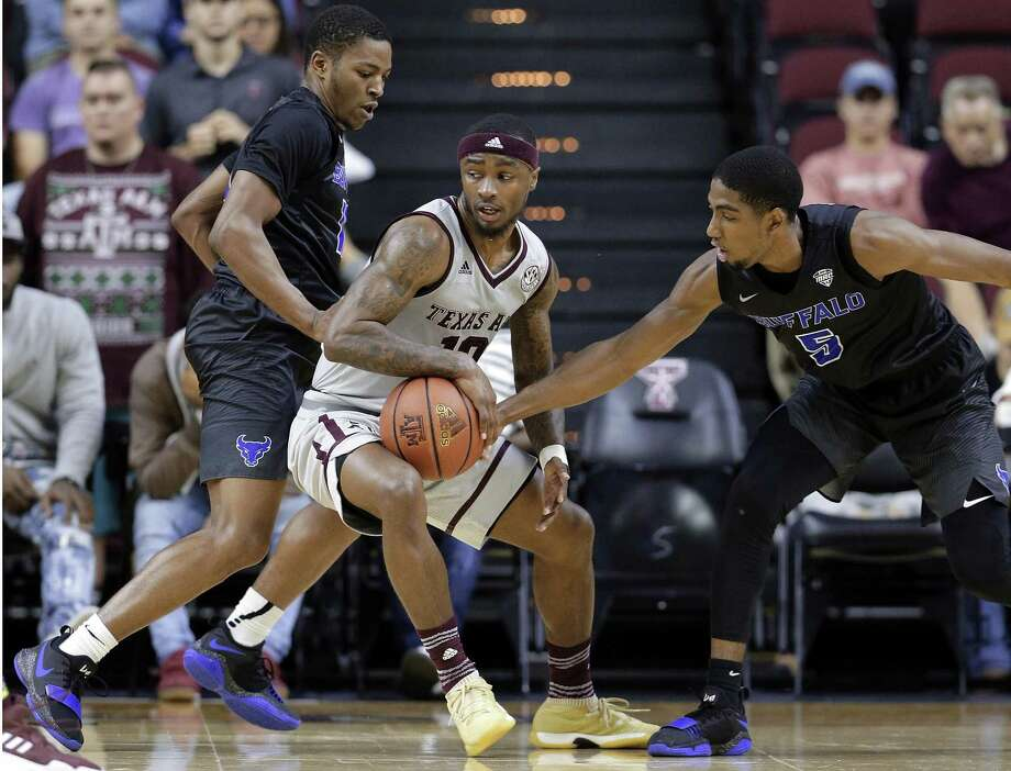 Texas A&M guard Duane Wilson (13) drives between Buffalo guard Wes Clark (10) and guard CJ Massinburg (5) during the second half of an NCAA college basketball game Thursday, Dec. 21, 2017, in College Station, Texas. (AP Photo/Michael Wyke) Photo: Michael Wyke, FRE / Associated Press / © Associated Press 2017