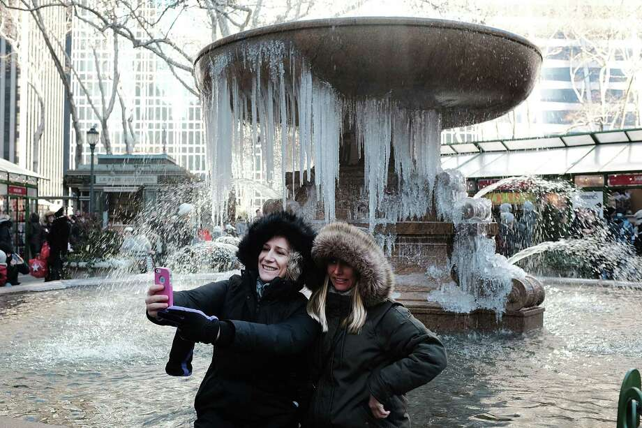 Two women take a selfie in front of a frozen fountain. Dangerously low temperatures and wind chills the central and eastern U.S. are making outdoor activity difficult for many Americans.   Photo: Spencer Platt, Staff / 2017 Getty Images