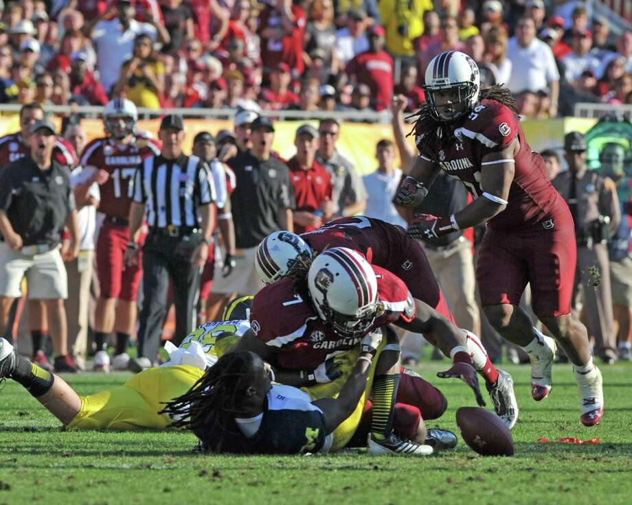 With one of college football's most memorable hits, Jadeveon Clowney (7) separated Vincent Smith from the ball and his helmet in the 2013 Outback Bowl. Photo: Al Messerschmidt, Stringer / 2013 Getty Images
