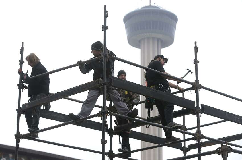 A crew works to erect a structure made of steel pipes Friday, Dec. 29, 2017, at HemisFair near the Henry B. Gonzalez Convention Center. Stages for musical performances, tents and other stuctures in the area just west of the Convention Center are being assembled for the upcoming New Year's Eve Celebration that will kick off San Antonio's 300th birthday celebration. The event is free and open to the public and opens at 4:00 p.m. . The event will feature interactive art, games, music and live theatrical performances. A wide array of food and drink options will be available.