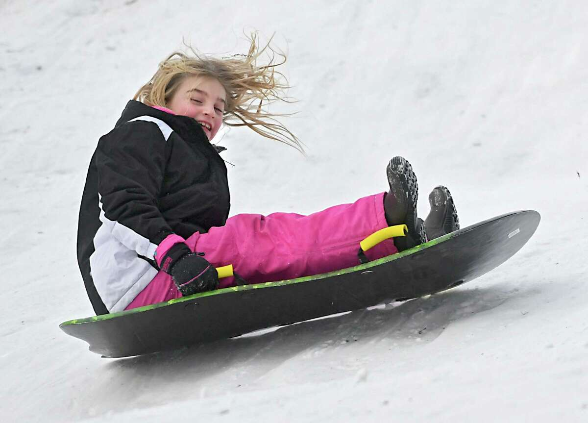 Sadie Pelletier of Glenville, 9, braves the bitter cold and finds fun sledding on a hill in Central Park on Friday, Dec. 29, 2017 in Schenectady, N.Y. In the 2020-2021 school year, New York is piloting a program that would allow districts to have remote learning instead of snow days.(Lori Van Buren / Times Union)