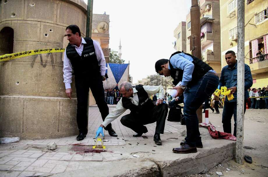 TOPSHOT - Egyptian security members and forensic police inspect the site of a gun attack outside a church south of the capital Cairo, on December 29, 2017. A gunman opened fire on a church, killing at least nine people before policemen shot him dead, state media and officials said.  / AFP PHOTO / Samer ABDALLAHSAMER ABDALLAH/AFP/Getty Images Photo: SAMER ABDALLAH / AFP or licensors