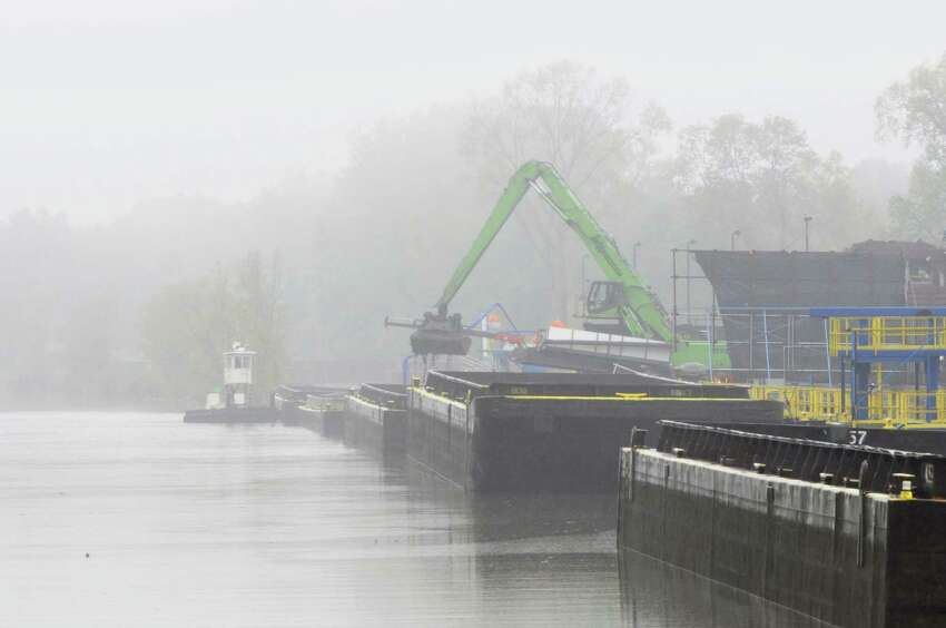 Workers unload PCB tainted sediment from a scow at the dewatering facility just below Lock 8 on the Champlain Cananl during a boat tour along the Champlain Canal and the Hudson River to see the PCB dredging process taking place on Thursday, Sept. 22, 2011, near Fort Edward. (Paul Buckowski / Times Union)