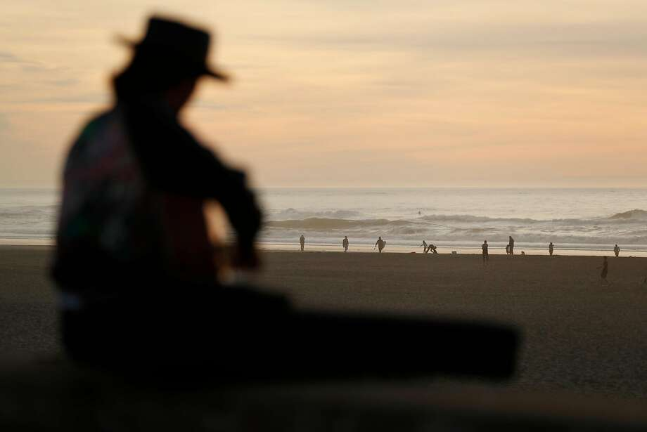 Jesse Schwartz of Guerneville plays guitar at Ocean Beach, a perfect place to contemplate the new year. Photo: Scott Strazzante, The Chronicle