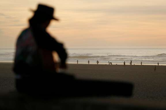 Jesse Schwartz of Guerneville plays guitar at Ocean Beach in San Francisco, Calif., on Thursday, December 28, 2017.