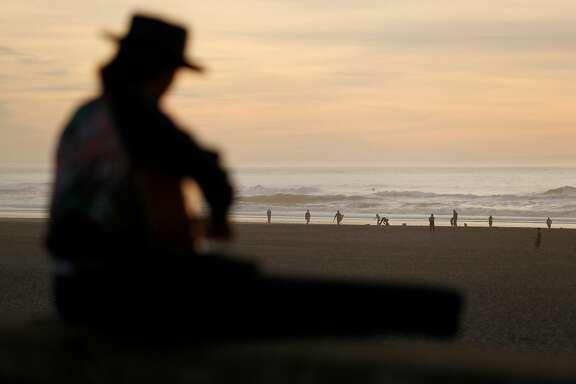 Jesse Schwartz of Guerneville plays guitar at Ocean Beach in San Francisco, Calif., on Thursday, December 28, 2017.