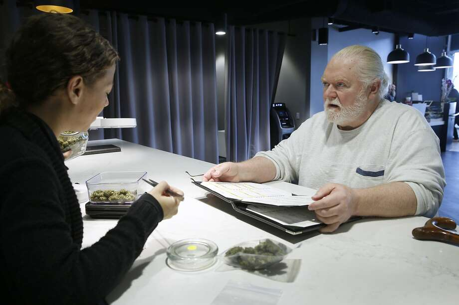Mark Henderson selects medicinal cannabis from Laura Sotak (left) at the Apothecarium's Castro dispensary in San Francisco. Photo: Paul Chinn, The Chronicle