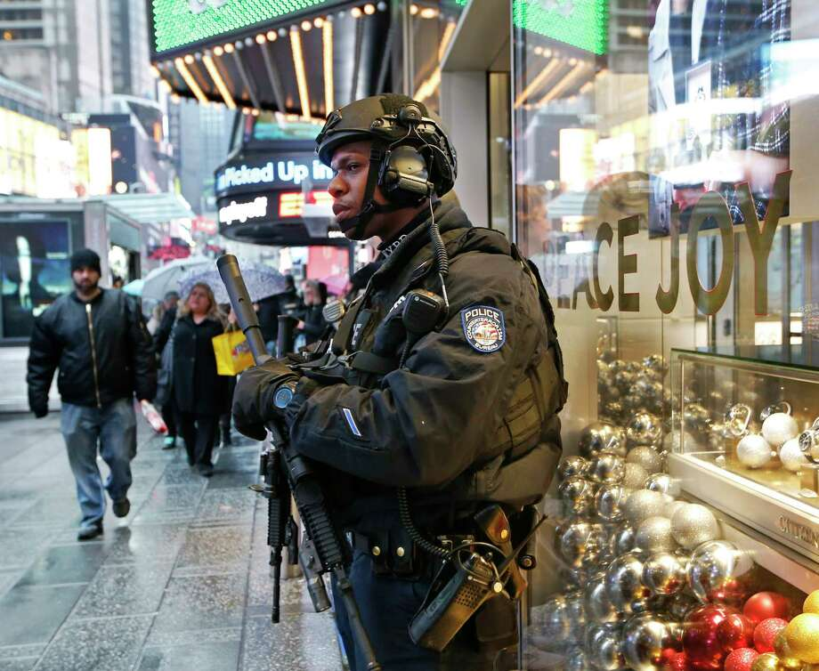 FILE - In this Dec. 29, 2016 file photo, a heavily armed counterterrorism officer takes shelter beneath an overhang above a store in Times Square in New York. New York Police Department officials say that while there are no specific or credible threats against the city, they are promising a bigger security detail than ever before at the Sunday, Dec. 31, 2017, New Year's Eve celebration in Times Square. (AP Photo/Kathy Willens, File) Photo: Kathy Willens / Copyright 2017 The Associated Press. All rights reserved.