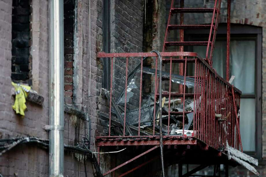 Charred items sit on the fire escape of an apartment building where more than 10 people died in fire a day earlier in the Bronx borough of New York, Friday, Dec. 29, 2017. New York City's deadliest residential fire in decades was accidentally lit by a boy playing with the burners on his mother's stove, officials said Friday. (AP Photo/Julio Cortez) Photo: Julio Cortez / Copyright 2017 The Associated Press. All rights reserved.