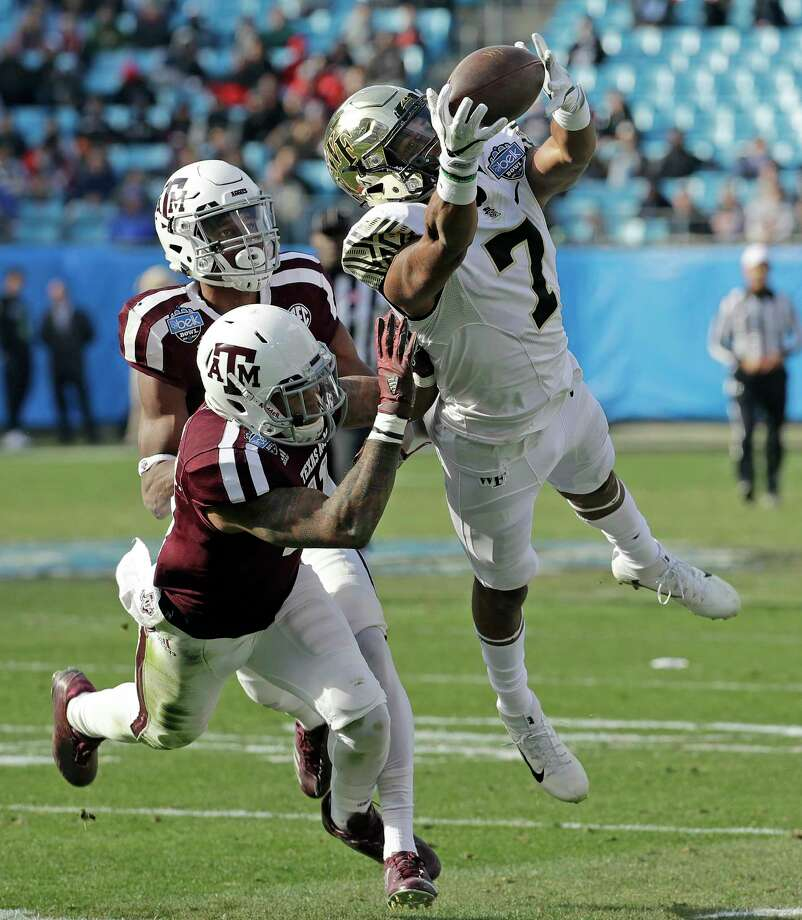 Wake Forest's Scotty Washington, right, extends himself to make a catch despite the best efforts of Texas A&M's Larry Pryor and Myles Jones in the first half of the Belk Bowl on Friday. Washington had nine catches for 138 yards and one touchdown. Photo: Chuck Burton, STF / Copyright 2017 The Associated Press. All rights reserved.
